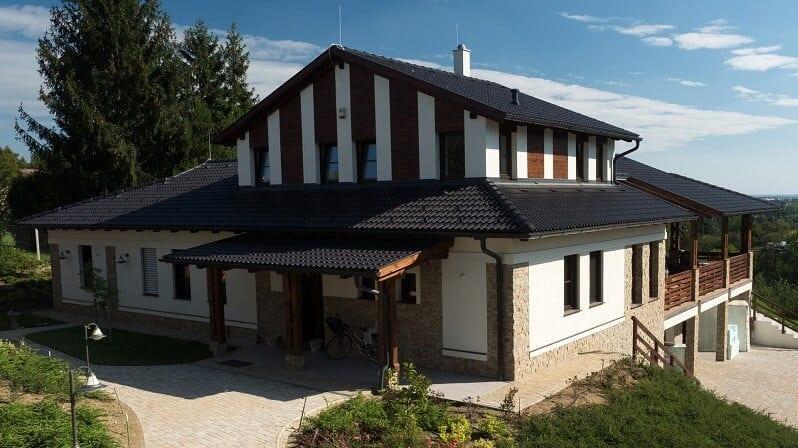 moderny-dom-cierna-strecha-biela-fasada-kombinovana-s-drevenym-a-kamennym-obkladom