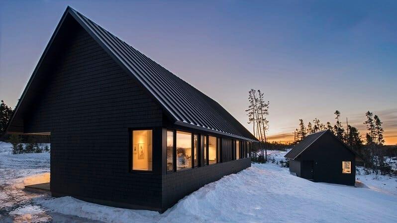 dom-s-garazou-obklad-z-ebenoveho-dreva-cierna-strecha-pritmie-vecer-zapad-slnka