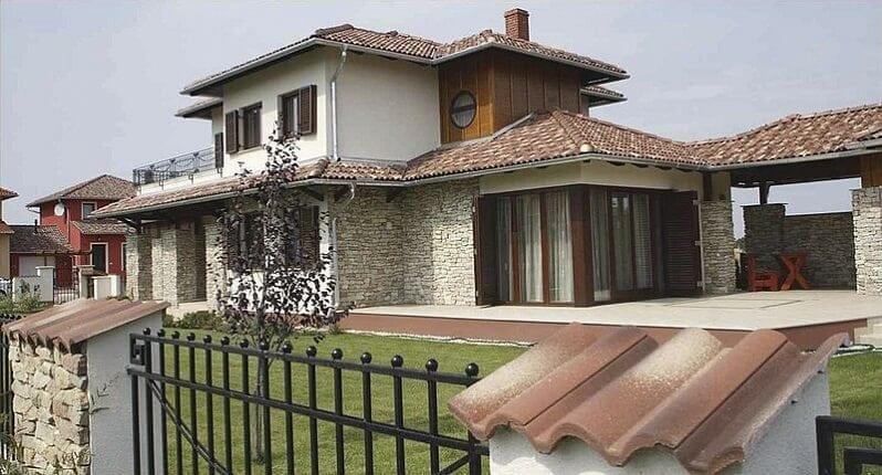 Melirovana-krytina-s-tmavsim-nadychom-do-cervena-rodinny-dom-s-terasou-a-zahradou-s-bielou-fasadou-a-kamennym-obkladom